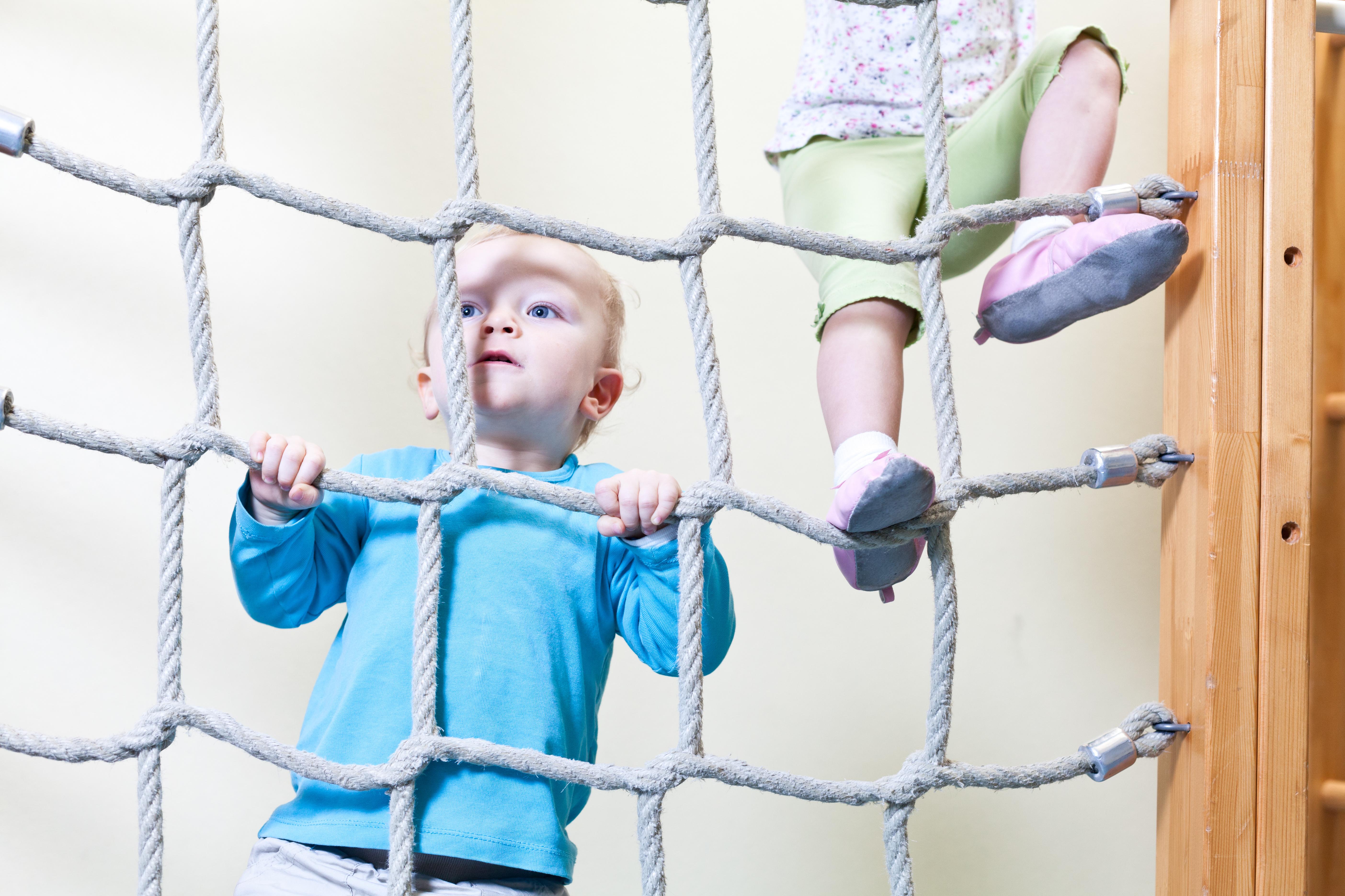 Junge klettert beim Kinderturnen